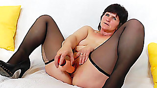 Granny stretches her holes with a vibrator